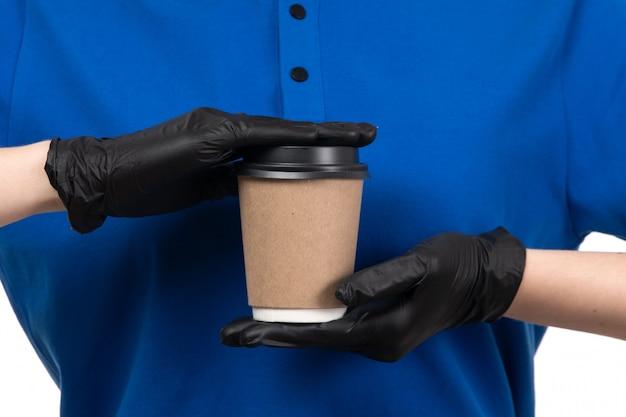 Une vue de face jeune courrier en uniforme bleu masque noir et gants tenant une tasse de café