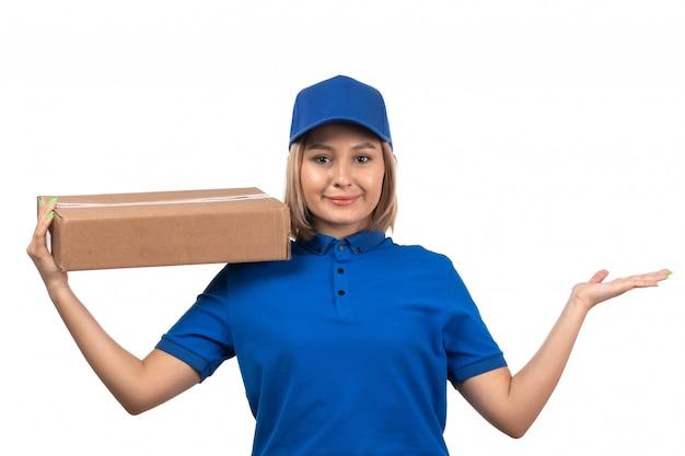 Une vue de face jeune courrier en uniforme bleu tenant le colis de livraison de nourriture avec le sourire sur son visage