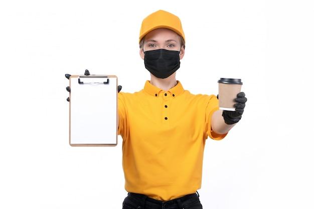 Une vue de face jeune courrier en uniforme jaune gants noirs et masque noir tenant le bloc-notes avec tasse à café
