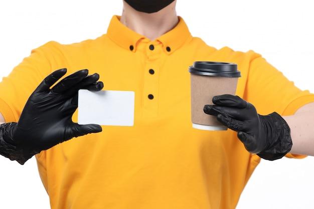 Une vue de face jeune courrier en uniforme jaune gants noirs et masque noir tenant une carte blanche et une tasse de café