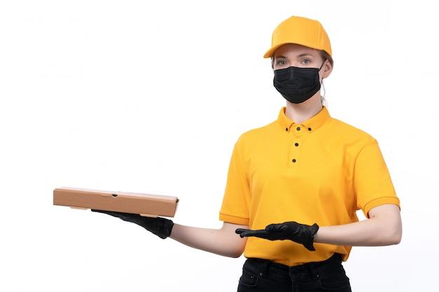 Une vue de face jeune courrier en uniforme jaune gants noirs et masque noir tenant le paquet de livraison de nourriture