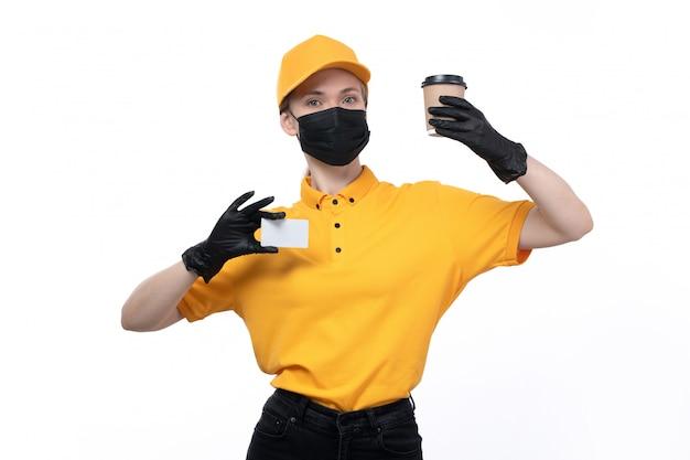 Une vue de face jeune courrier en uniforme jaune gants noirs et masque noir tenant une tasse de café et une carte blanche