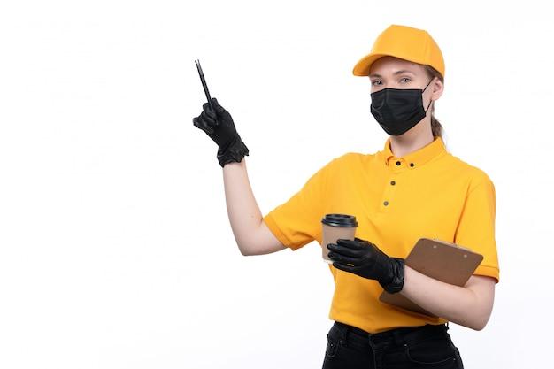 Une vue de face jeune courrier en uniforme jaune gants noirs et masque noir tenant une tasse de café et un stylo avec bloc-notes