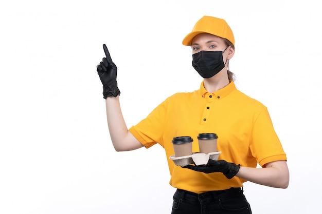 Une vue de face jeune courrier en uniforme jaune gants noirs et masque noir tenant des tasses à café montrant le signe du doigt