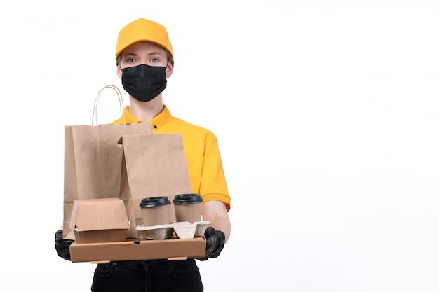 Une vue de face jeune courrier en uniforme jaune gants noirs et masque noir tenant des tasses à café et des paquets de livraison de commande