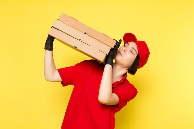 Une vue de face jeune courrier en uniforme rouge gants noirs et bonnet rouge tenant des boîtes