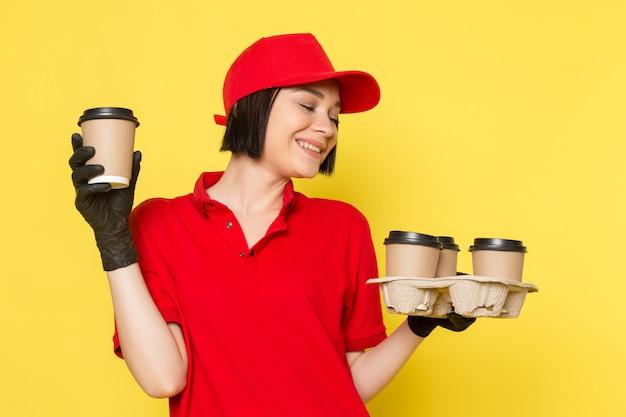Une vue de face jeune courrier en uniforme rouge gants noirs et bonnet rouge tenant des tasses à café