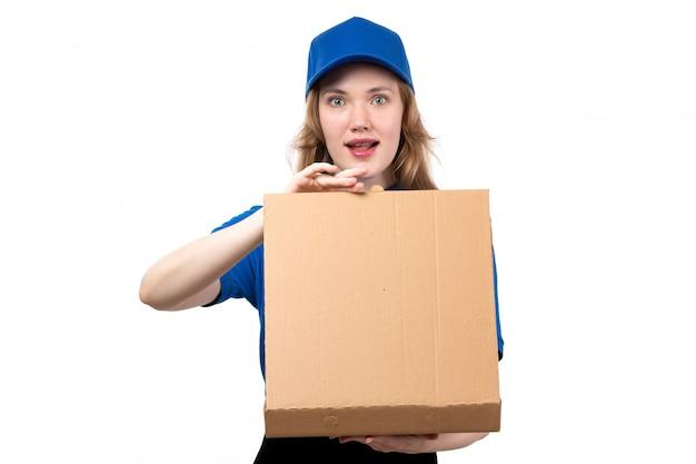 Une vue de face jeune courrier en uniforme tenant le colis de livraison et l'ouvrir avec une expression curieuse