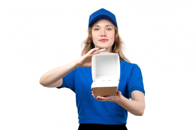 Une vue de face jeune courrier en uniforme tenant un colis de livraison vide souriant