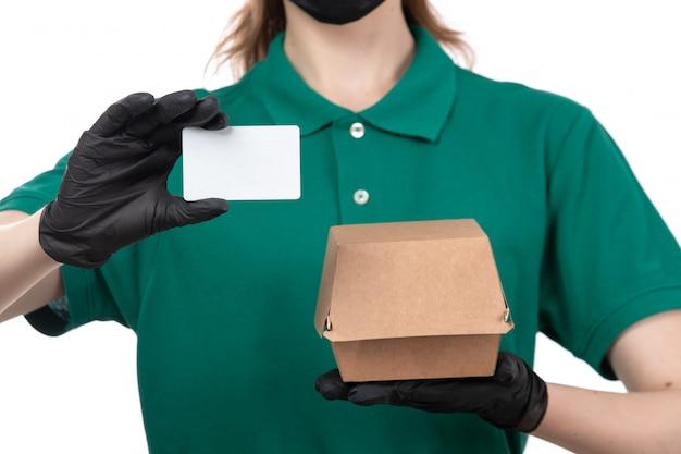 Une vue de face jeune courrier en uniforme vert gants noirs et masque noir tenant le colis de livraison de nourriture et carte blanche