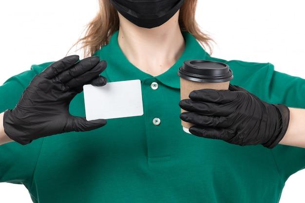 Une vue de face jeune courrier en uniforme vert gants noirs et masque noir tenant une tasse de café et une carte blanche