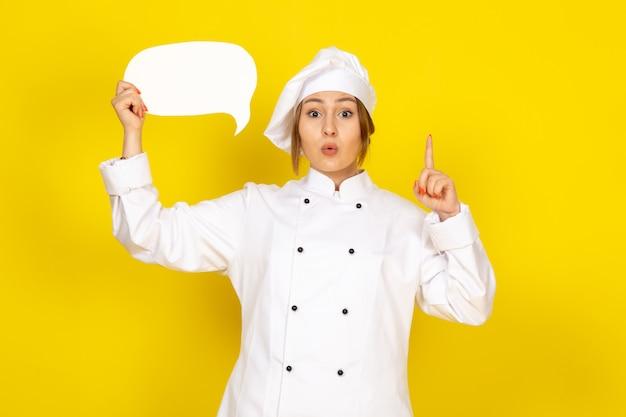 Une vue de face jeune cuisinier en costume de cuisinier blanc et bonnet blanc tenant une pancarte blanche sur le jaune