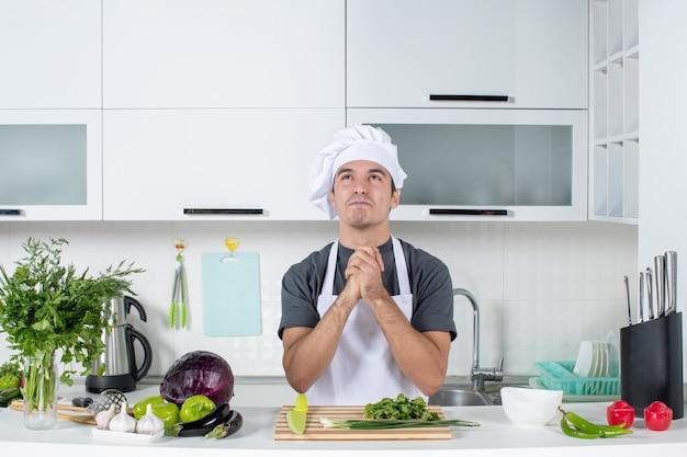 Vue de face jeune cuisinier satisfait en uniforme les mains jointes