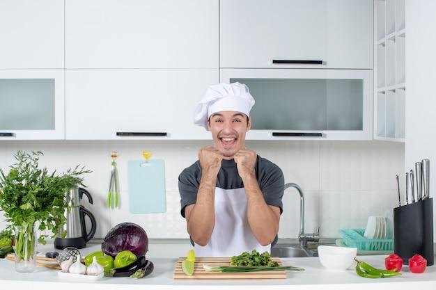Vue de face jeune cuisinier en uniforme exprimant ses sentiments