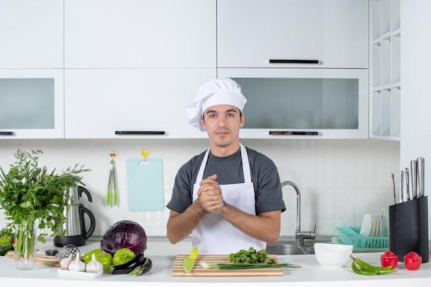 Vue de face jeune cuisinier en uniforme les mains jointes
