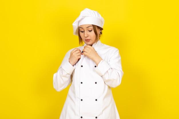 Une vue de face jeune cuisinière en costume de cuisinier blanc et bonnet blanc fixant son costume sur le jaune