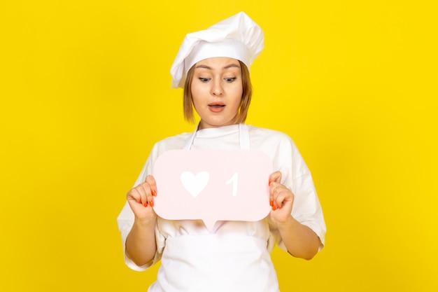 Une vue de face jeune cuisinière en costume de cuisinier blanc et bonnet blanc tenant une pancarte rose sur le jaune