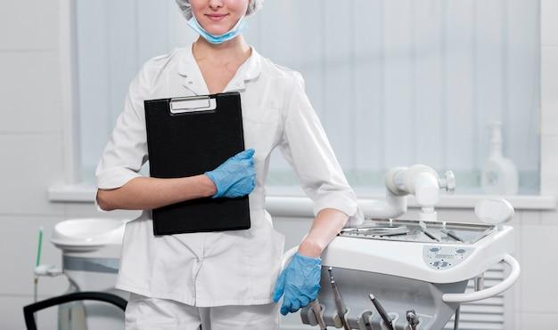 Vue de face jeune dentiste tenant le presse-papiers