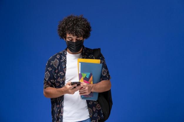 Vue de face jeune étudiant masculin portant un masque noir avec sac à dos contenant des fichiers et en utilisant son téléphone sur le fond bleu.