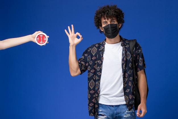 Vue de face jeune étudiant masculin portant un masque noir avec sac à dos montrant bien signe sur fond bleu.