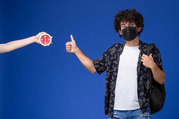 Vue de face jeune étudiant masculin portant un masque noir avec sac à dos montrant comme signe sur fond bleu clair.