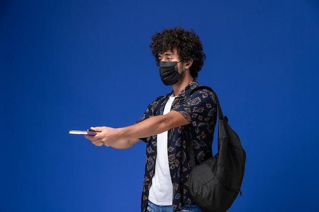 Vue de face jeune étudiant masculin portant un masque noir avec sac à dos tenant un cahier et un stylo sur fond bleu.