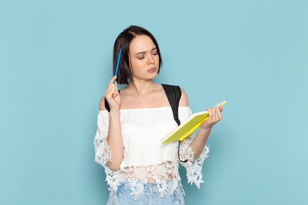 Vue de face jeune étudiante en chemise blanche jean bleu et sac noir en écrivant des notes sur l'espace bleu étudiante université école