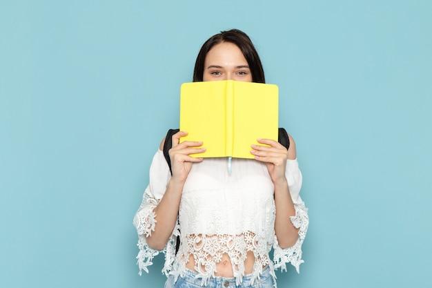 Vue de face jeune étudiante en chemise blanche jeans bleu et sac noir tenant un cahier jaune sur l'espace bleu étudiante université école