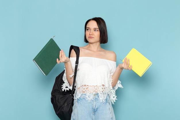 Vue de face jeune étudiante en chemise blanche jeans bleu et sac noir tenant des cahiers sur le plancher bleu étudiante université enseigner à l'école