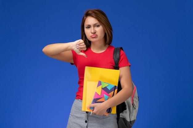 Vue de face jeune étudiante en chemise rouge portant un sac à dos contenant des fichiers et un cahier sur fond bleu.