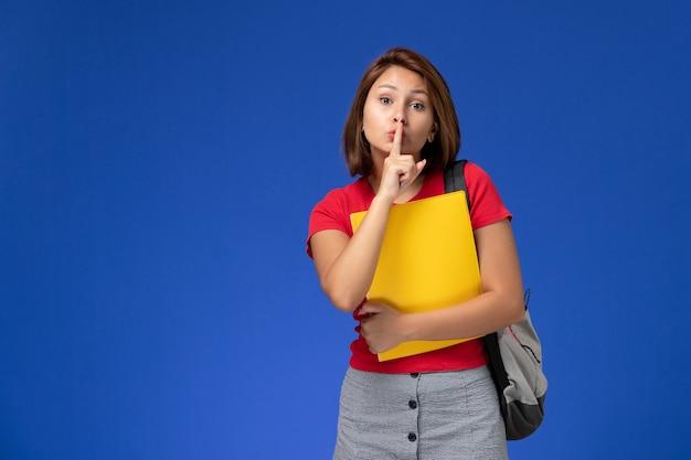 Vue de face jeune étudiante en chemise rouge avec sac à dos tenant des fichiers jaunes showign silence signe sur fond bleu clair.