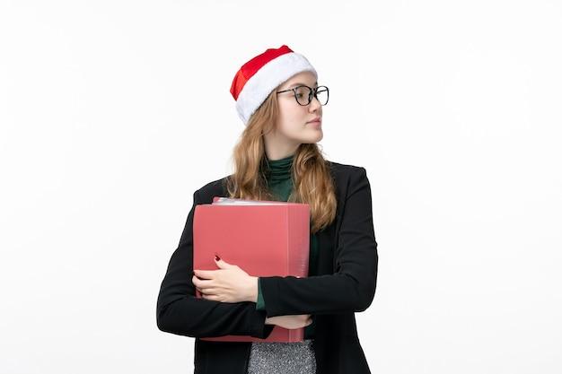 Vue de face jeune étudiante avec des fichiers sur le bureau blanc livre école college
