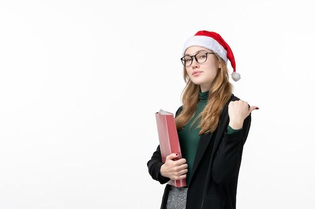 Vue de face jeune étudiante avec des fichiers sur un mur blanc book school college