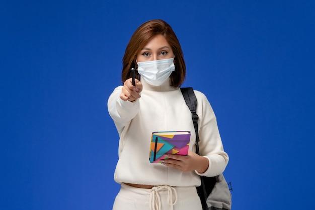 Vue de face jeune étudiante en maillot blanc portant un masque avec sac et cahier avec stylo sur le mur bleu