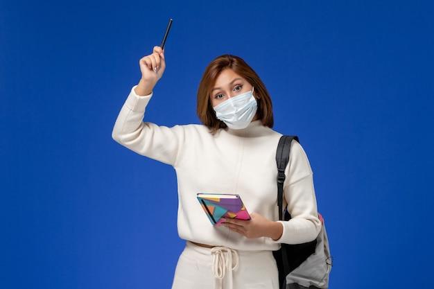 Vue De Face Jeune étudiante En Maillot Blanc Portant Un Masque Avec Sac Et Cahier Avec Stylo Sur Le Mur Bleu Photo gratuit