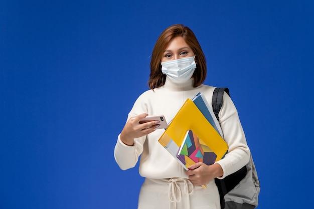Vue de face jeune étudiante en maillot blanc portant un masque avec sac et cahiers et à l'aide de son téléphone sur le mur bleu