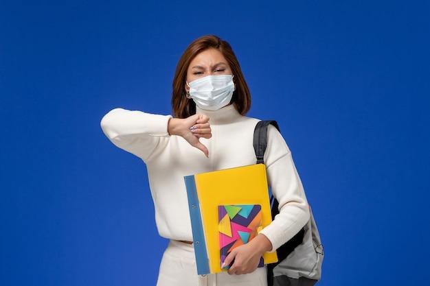 Vue de face jeune étudiante en maillot blanc portant un masque avec sac et cahiers sur le mur bleu