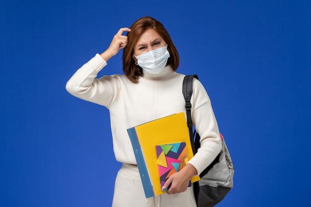Vue de face jeune étudiante en maillot blanc portant un masque avec sac et cahiers pensant sur le mur bleu