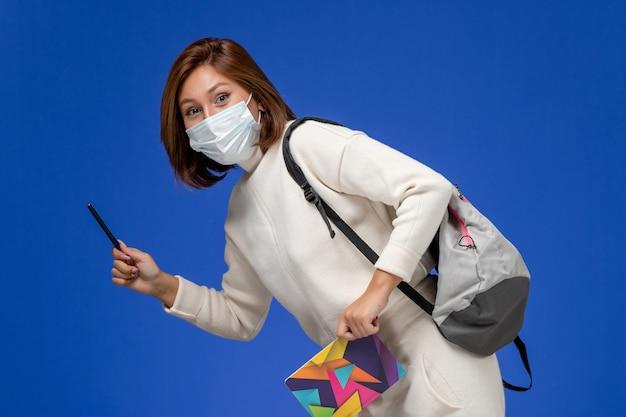 Vue de face jeune étudiante en maillot blanc portant un masque avec sac et stylo avec cahier sur le mur bleu