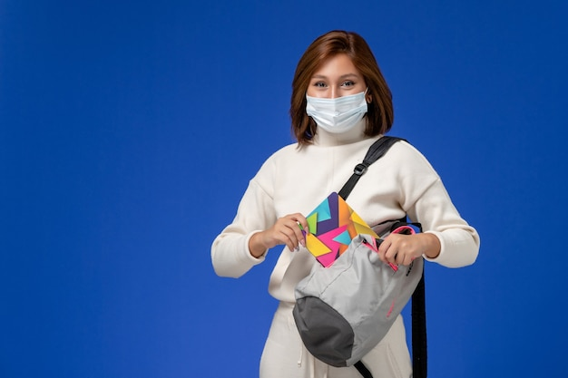 Vue de face jeune étudiante en maillot blanc portant un masque et un sac tenant un cahier sur le mur bleu