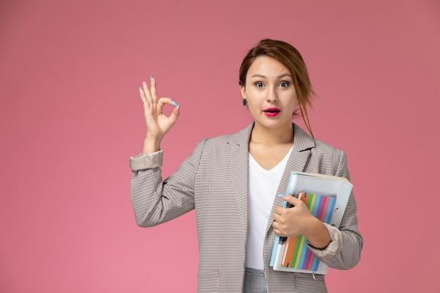 Vue de face jeune étudiante en manteau gris avec des cahiers sur fond rose leçons étude de collège universitaire