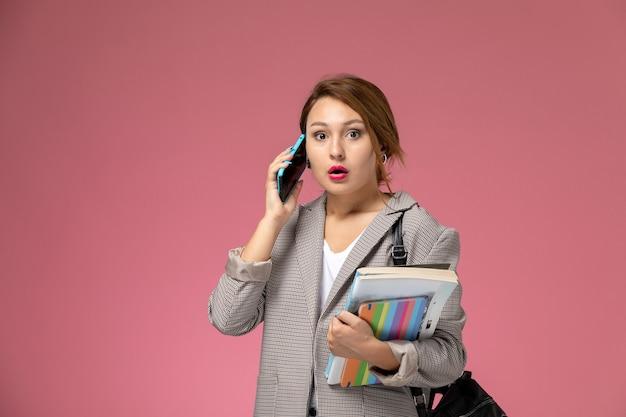 Vue de face jeune étudiante en manteau gris avec des cahiers talkign sur le téléphone sur les leçons de fond rose étude de collège universitaire
