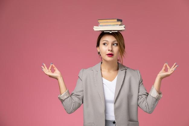 Vue de face jeune étudiante en manteau gris posant avec des livres sur sa tête sur fond rose leçons étude de collège universitaire