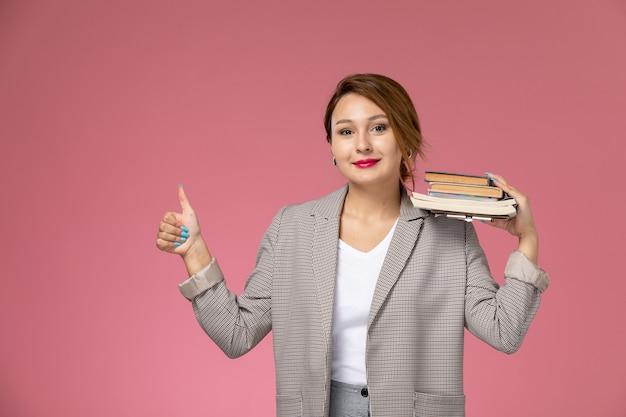 Vue de face jeune étudiante en manteau gris posant tenant des livres avec le sourire sur les leçons de fond rose étude de collège universitaire