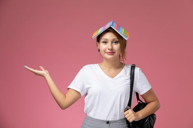 Vue de face jeune étudiante en t-shirt blanc avec cahier et sac posant et avec un léger sourire sur fond rose leçon university college study book