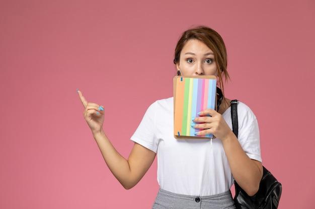 Vue de face jeune étudiante en t-shirt blanc avec cahier et sac posant sur le livre d'étude du collège universitaire leçon fond rose