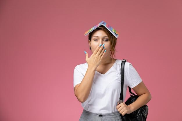 Vue de face jeune étudiante en t-shirt blanc et pantalon gris avec cahier sur sa tête sur le fond rose leçons college college