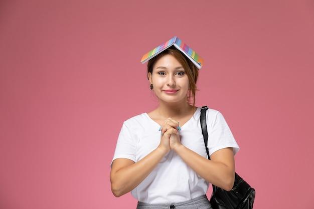 Vue de face jeune étudiante en t-shirt blanc avec sac et écouteurs posant et souriant avec un cahier sur sa tête sur fond rose le livre d'étude du collège