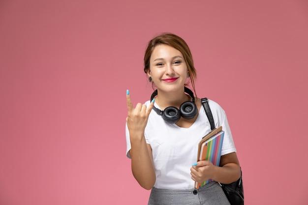 Vue de face jeune étudiante en t-shirt blanc avec sac et écouteurs style rocker posant et souriant sur fond rose leçon université cahier d'étude