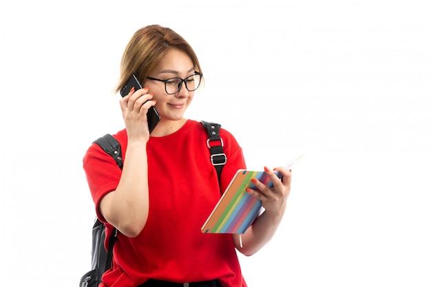 Une vue de face jeune étudiante en t-shirt rouge portant un sac noir tenant un cahier et un smartphone noir parlant le blanc